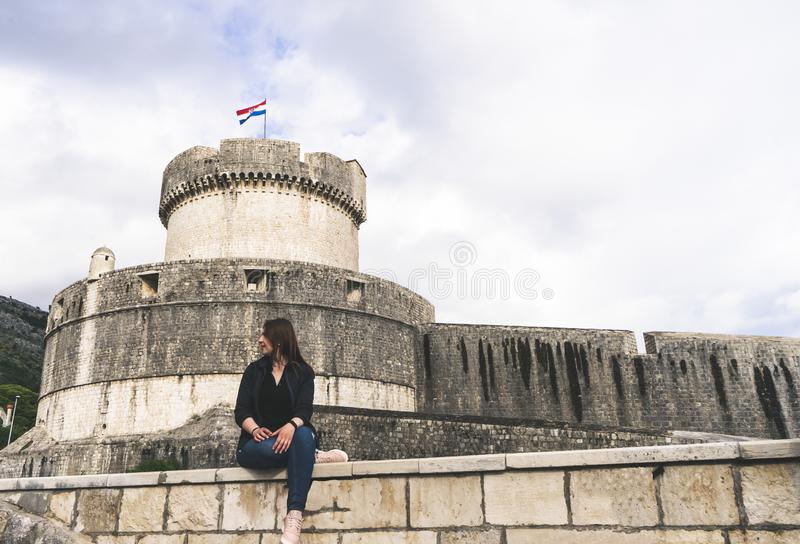 Exterior view of the wall around Dubrovnik (Croatia), city on the Adriatic Sea. Girl tourist sitting in a wall. Town, house, historic, building stock images