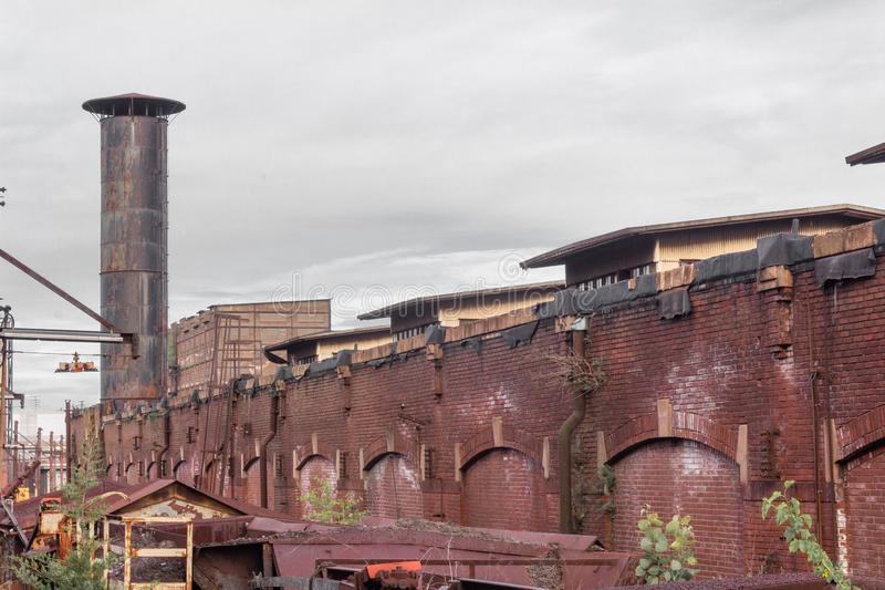 Exterior view of a warehouse district, old brick architecture, smokestack, rusting metal structures stock photography