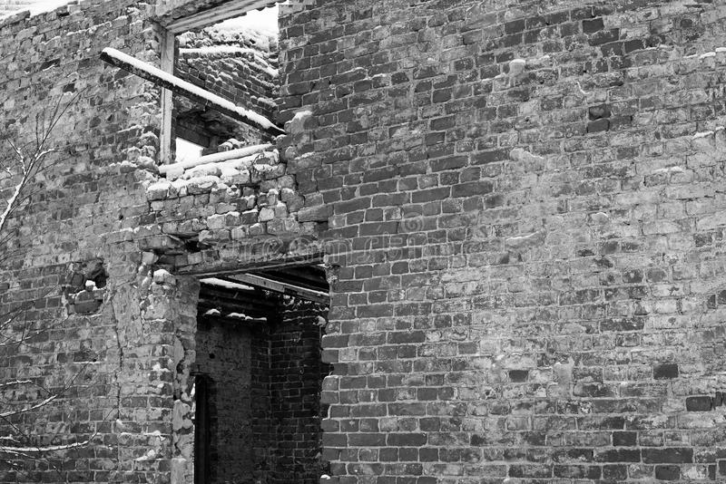 Exterior wall of an abandoned ruined brick house with a window and a doorway in winter, black and white photo stock image