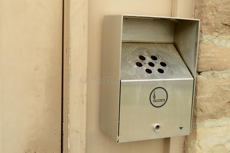Exterior Wall Mounted Ashtray. Closeup image of an exterior wall mounted smokers ashtray for smutting out cigarettes before entrance to the building stock images