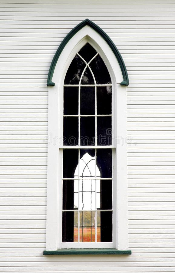 Exterior of church with Gothic window. Exterior wall of white church looking through singular Gothic window royalty free stock photos