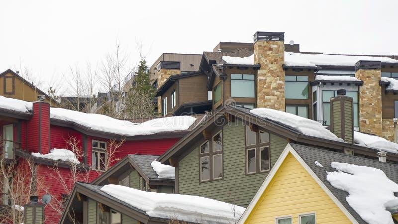Exteriores caseros del marco del panorama con el apartadero horizontal de la pared y la nieve gruesa en los tejados fotos de archivo libres de regalías