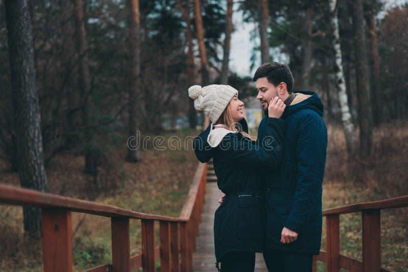 Exteriores felizes dos pares novos loving junto em acolhedor aquecem a caminhada na floresta imagens de stock