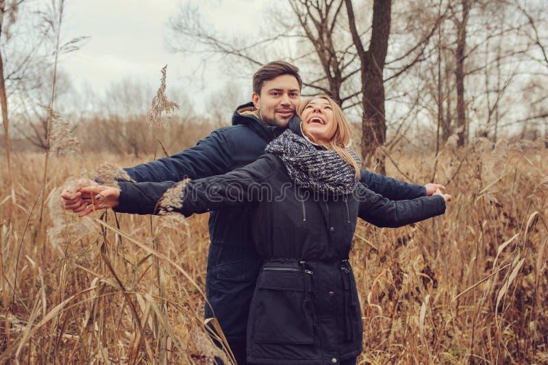 Exteriores felizes dos pares novos loving junto em acolhedor aquecem a caminhada na floresta do outono foto de stock