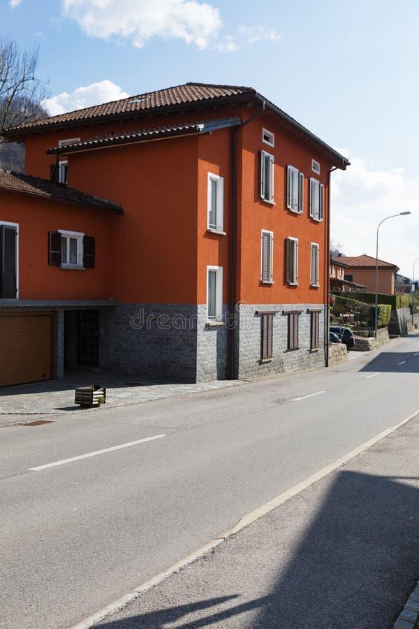 Exteriores vermelhos da casa na estrada fotos de stock