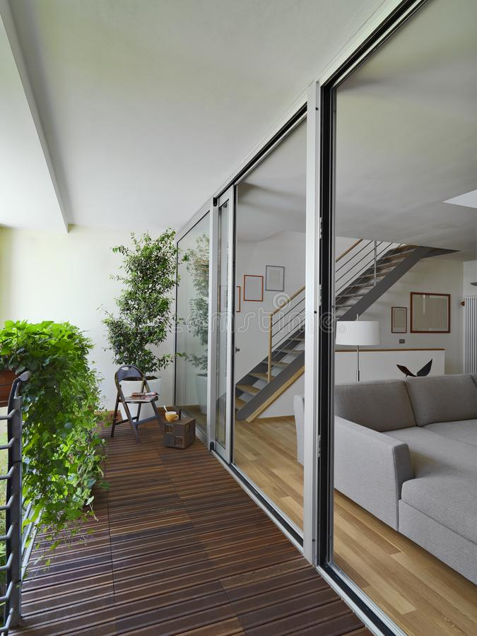 Exteriors shots of a modern balcony. With wood floor overlooking on the modern living room and staircase stock image