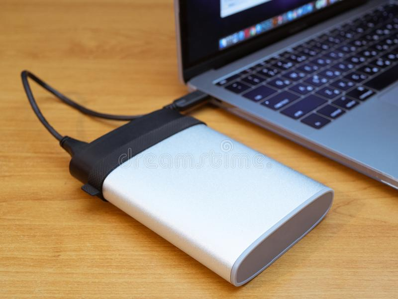 External disk drive connected to laptop by wire. Portable external disk drive connected to laptop by wire. data backup information concept stock image