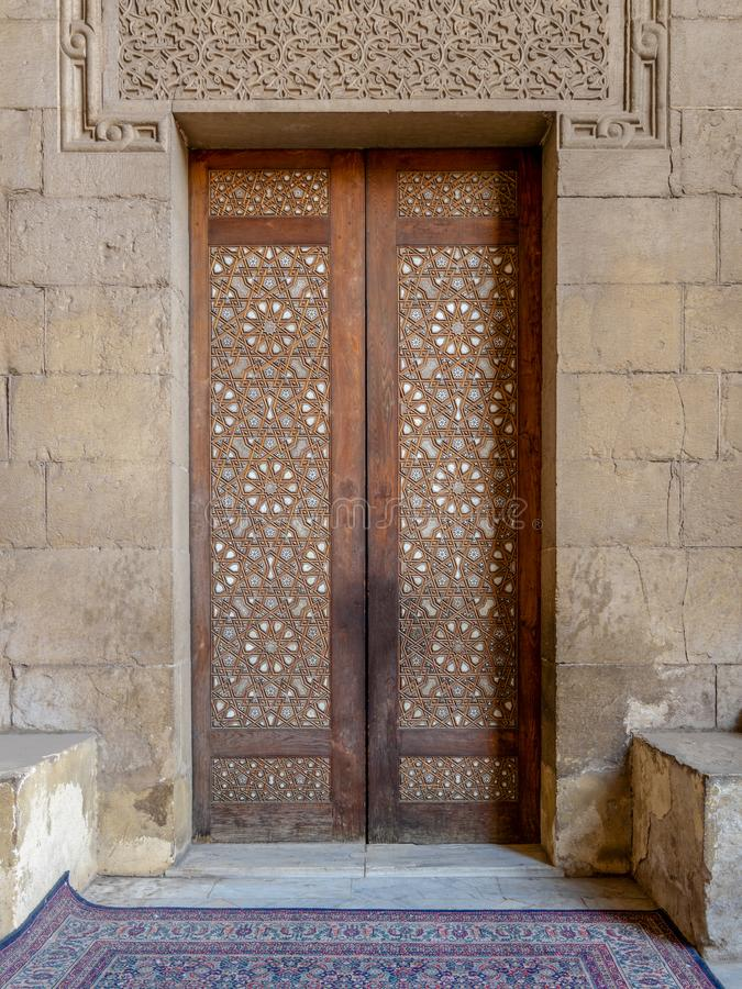 External old arabesque decorated wooden door leading to al Rifai Mosque, Cairo, Egypt. External old arabesque decorated wooden door leading to al Rifai Mosque royalty free stock photo