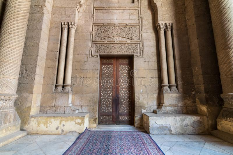 External old decorated bricks stone wall with arabesque decorated wooden door framed by stone ornate cylindrical columns. Leading to al Rifai Mosque, Old Cairo stock photos