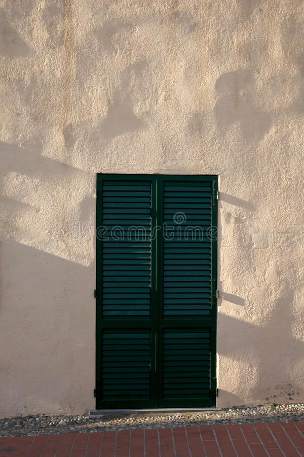 External old green metal door and a plaster wall. External old metal door and a plaster wall royalty free stock images