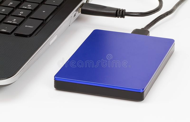 Externe opslag die met laptop door usbkabel wordt verbonden op wit bureau stock afbeelding