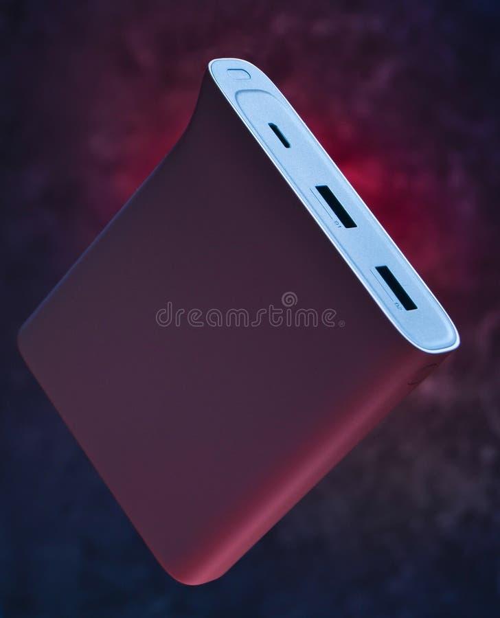 Externe tragbare Batterieleistungsbank für Smartphones und andere Geräte auf einem dunklen konkreten Hintergrund Mystisches Licht stockfotos