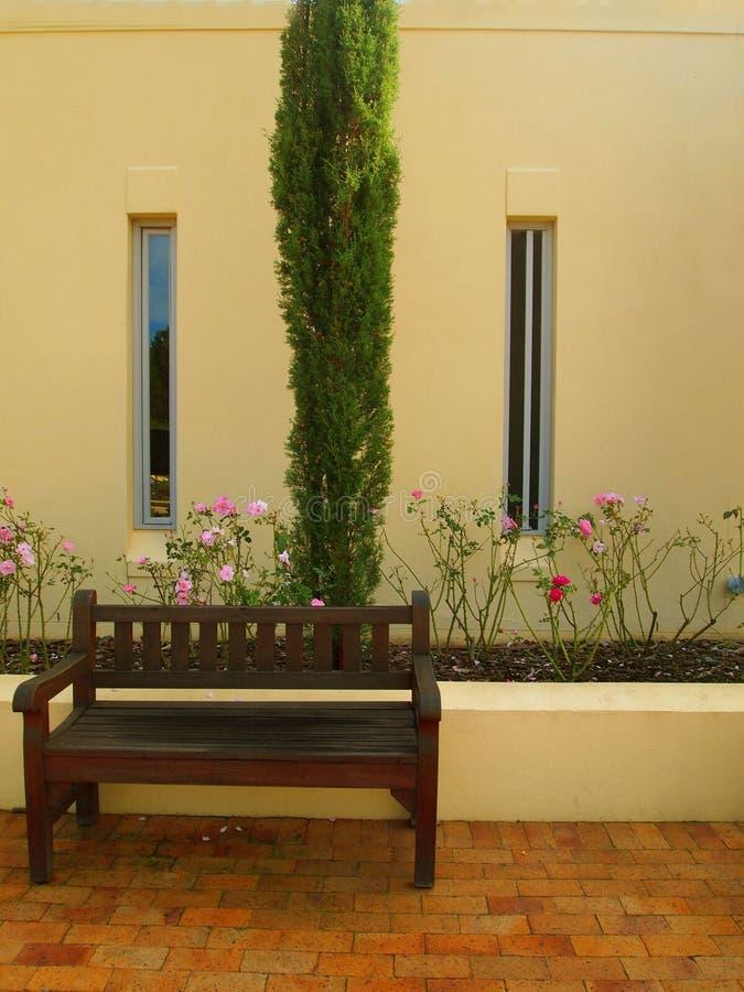 Externe voorgevel van plattelandshuis met bomen en bloembedden stock afbeelding