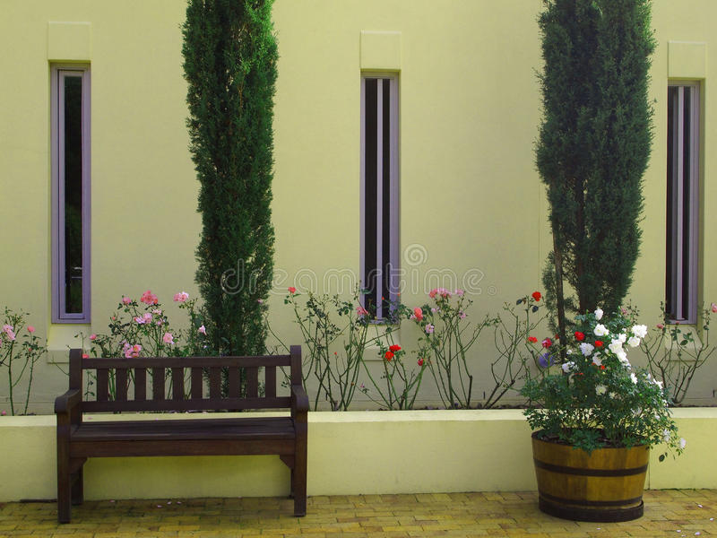 Externe voorgevel van plattelandshuis met cipressen en flowerbe royalty-vrije stock afbeeldingen