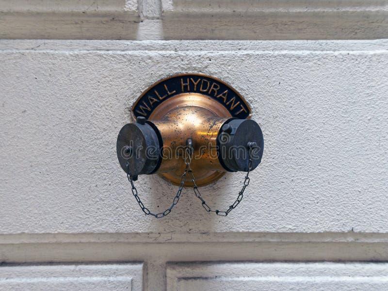 Externer Hydrant auf Steinwand lizenzfreies stockfoto