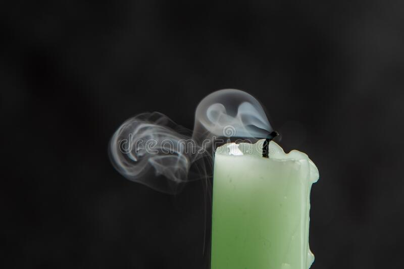 Extinct light green candle with spectacular, abstract smoke on a black background.  stock photography