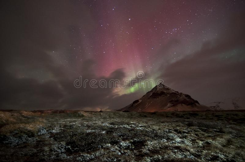 Extinct volcano covered by snow under red and green aurora borealis stock photos
