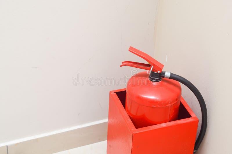 Extincteur rouge dans un conteneur en m?tal dans le coin d'un mur blanc S?curit? photos stock