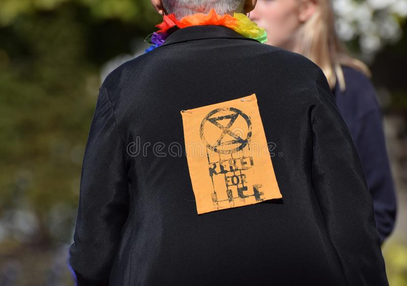 Extinction Rebellion Activist in the UK with a Rebel for Life sign pinned to the back of her coat. Extinction Rebellion abbreviated as XR is a socio-political royalty free stock photos