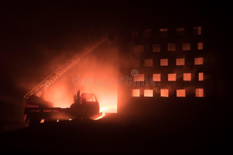 Extinga el fuego de una casa privada en la noche Juegue el coche de bomberos con la escalera larga y el edificio ardiente en la n imagenes de archivo