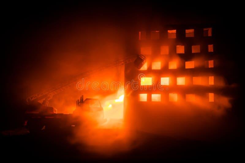 Extinga el fuego de una casa privada en la noche Juegue el coche de bomberos con la escalera larga y el edificio ardiente en la n foto de archivo