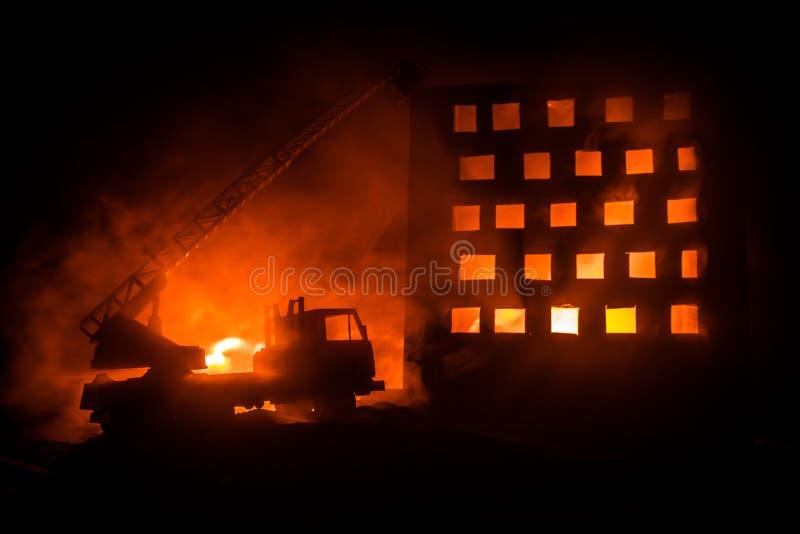 Extinga el fuego de una casa privada en la noche Juegue el coche de bomberos con la escalera larga y el edificio ardiente en la n fotos de archivo