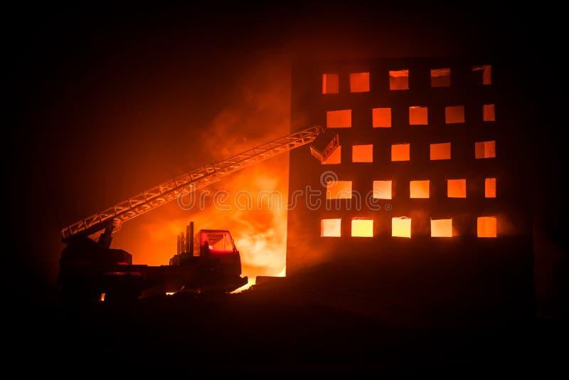 Extinga o fogo de uma casa privada na noite Brinque o carro de bombeiros com escada longa e construção ardente na noite Conceito  imagens de stock