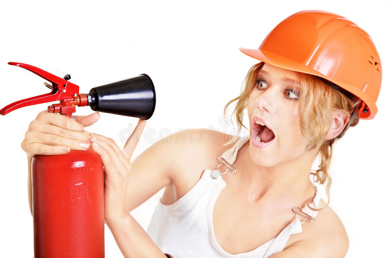 Extinguisher. Portrait of the beautiful joyful girl in an orange helmet with a fire extinguisher stock photography