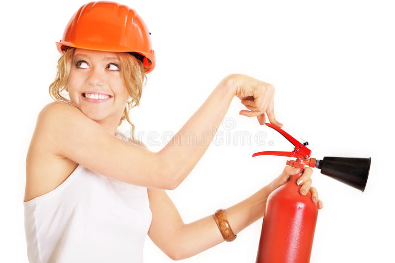 Extinguisher. Portrait of the beautiful joyful girl in an orange helmet with a fire extinguisher stock photos