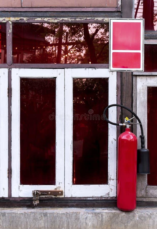 Extintor en el lado de una ventana de madera vieja en o delantero imagen de archivo libre de regalías
