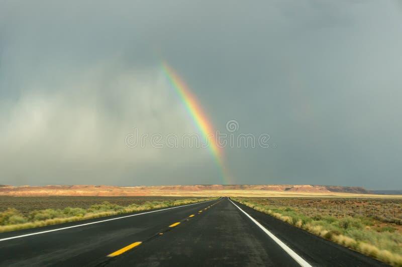 Extrémité d'un arc-en-ciel sur un noir une route, Amérique occidentale du sud photo stock