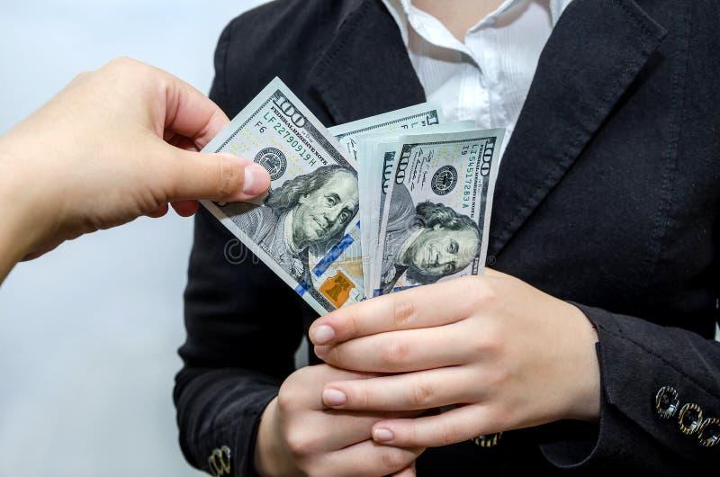 Extração de uma nota de dólar de uma pilha de dinheiro As mãos fêmeas guardam o dinheiro, nas denominações de 100 dólares foto de stock royalty free