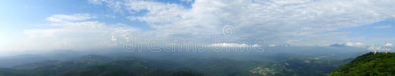 Extra breed panorama van bergen in April met sneeuwheuvels, blauwe hemel met wolken stock afbeeldingen
