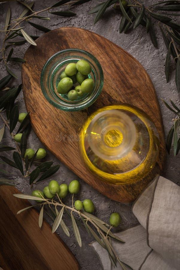 Extra eerste persing in glasfles met tak van olijven op rustieke achtergrond Het bekijken Camera stock foto