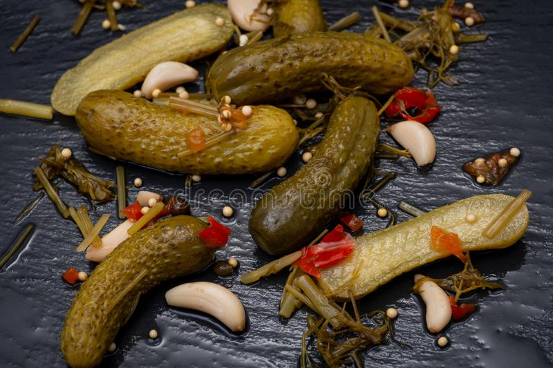 Extra Fine Cornichons - minuscule sour French pickles on natural stone background. Mini French style Gherkin Cucumbers stock photo
