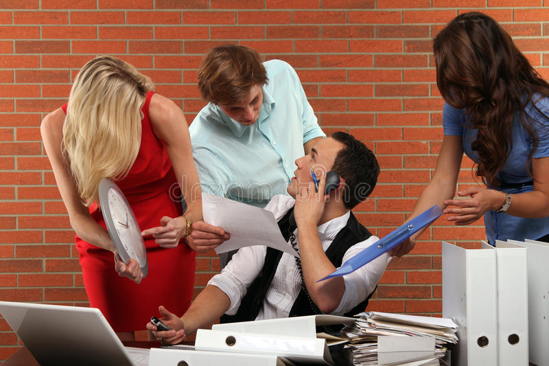 Extra hours. Multitasking business scene with some colleagues and typical business stuff and symbols royalty free stock photos