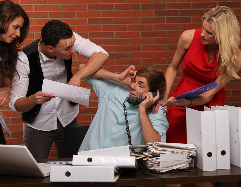 Extra hours. Multitasking business scene with some colleagues and typical business stuff and symbols stock image