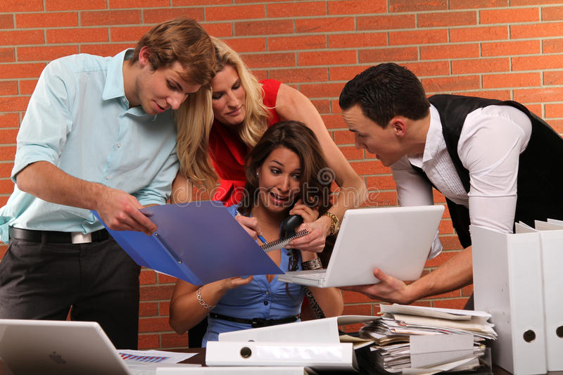 Extra hours. Young business woman is having stress with to much work and her colleagues stock photography