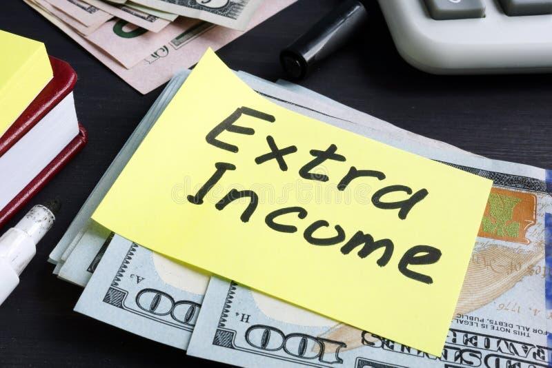 Extra inkomst som är skriftlig på ett stycke av papper och kassa royaltyfri bild