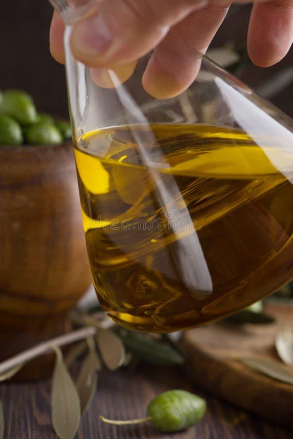 Extra jungfrulig olivolja i glasflaska i handen med oliv på lantlig bakgrund eyes den härliga kameran för konst mode som fulla ka royaltyfria bilder