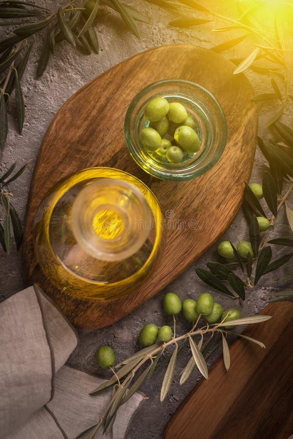 Extra jungfrulig olivolja i glasflaska med filialen av oliv på lantlig bakgrund låg tangent med solilsken blick från rätsida royaltyfri bild