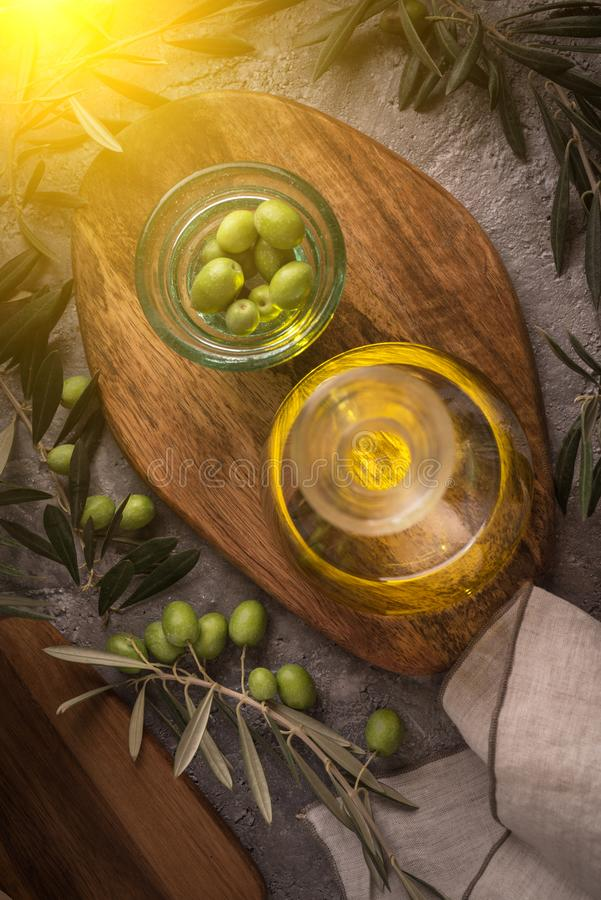 Extra jungfrulig olivolja i glasflaska med filialen av oliv på lantlig bakgrund låg tangent med solilsken blick från vänster sida arkivbild