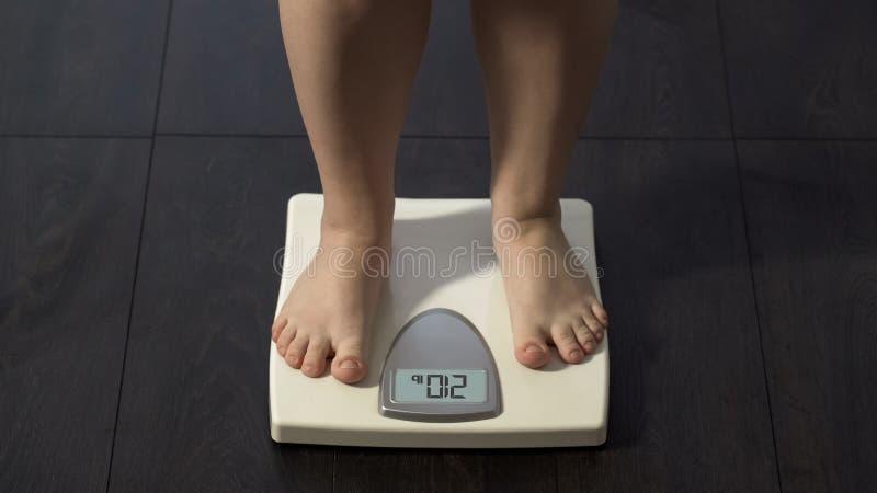 Extra lichaamsgewicht, wijfje die op schalen bevinden zich thuis om zwaarlijvig dieetresultaat te controleren, stock afbeeldingen