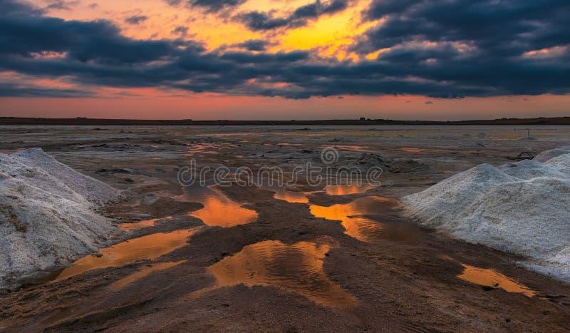 Extracción de sal en el lago durante puesta del sol imagenes de archivo