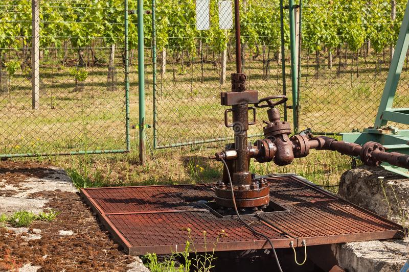 Extraction of good quality oil. Oil well pumpjack on vineyard in Czech Republic. Southern Moravia Region. Extraction of good quality oil. Oil well pumpjack on royalty free stock photo