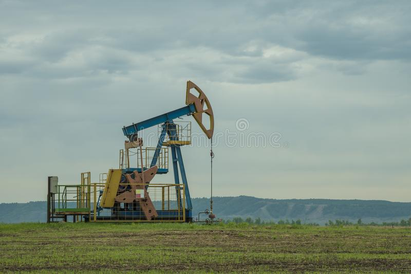 Extraction oil drilling pump, fuel production. Black gold. against the background of the sky of the mountains. barrel oil stock photography