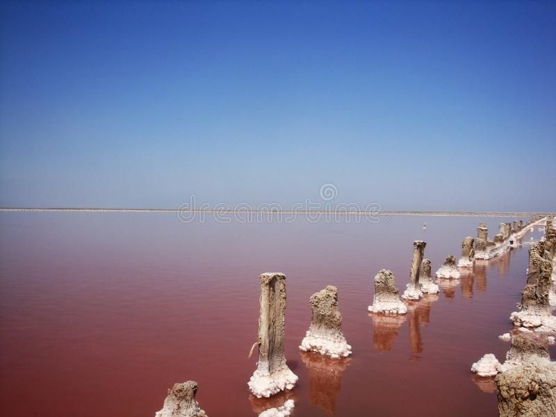 Extraction of salt in the estuary with red water. Salt pillars. The old weathered posts stand in the dry ground and human footprints on the salt peel at sunset royalty free stock photo
