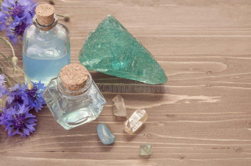 Extracto azul del agua azul del aciano en la botella de cristal, minerales, sal y flores en fondo marrón de madera fotos de archivo