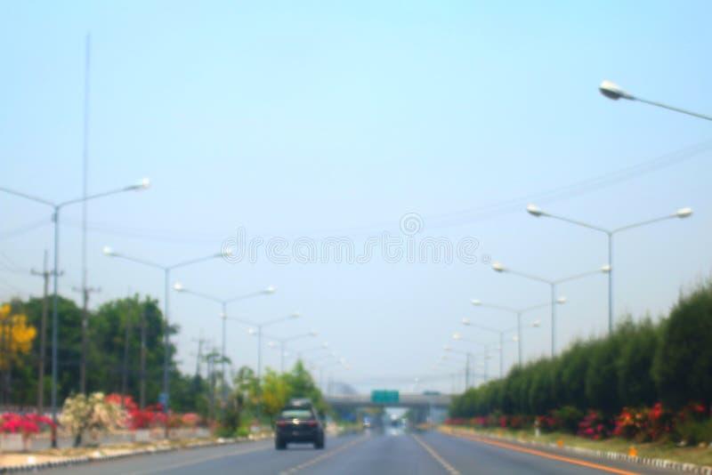 Extracto borroso del fondo del camino y del coche de la manera de largo camino en ciudad con el coche imagen de archivo libre de regalías