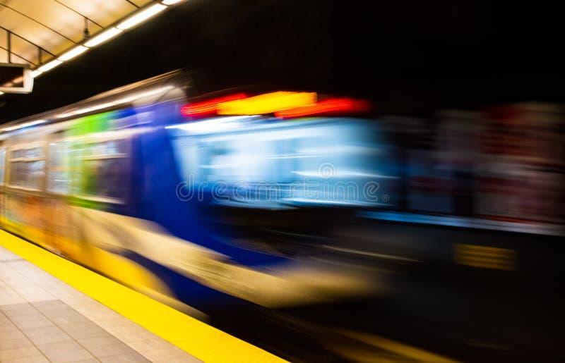 Extracto colorido con la falta de definición de movimiento del metro que sale la plataforma de la estación foto de archivo